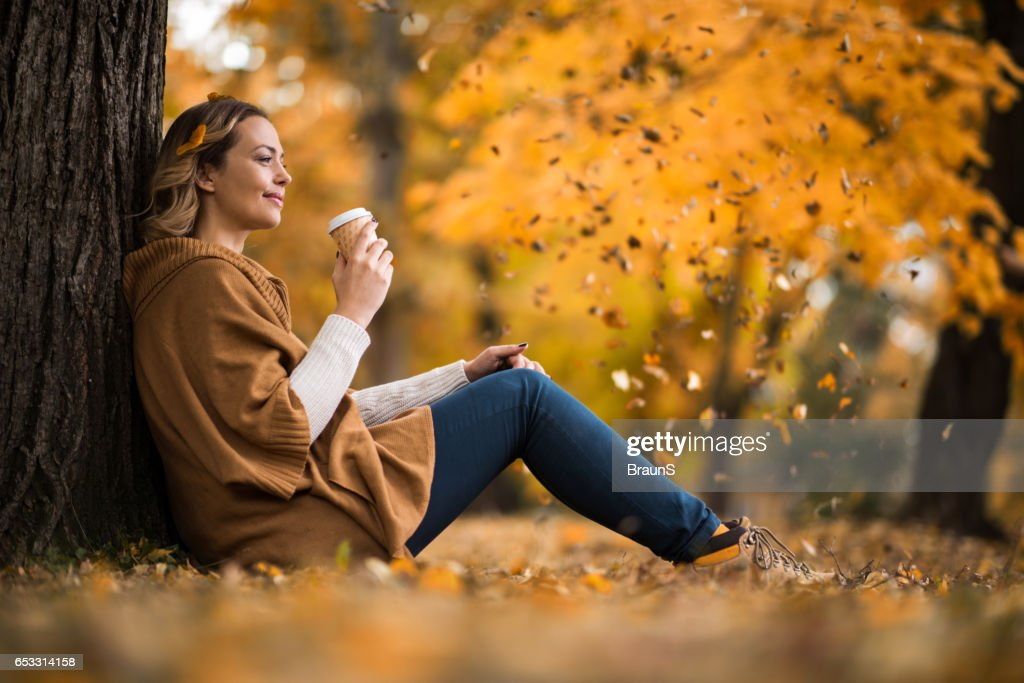 Smiling woman enjoying in coffee at the park. : Bildbanksbilder