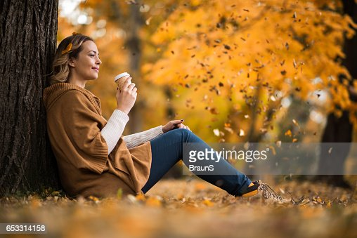 Smiling woman enjoying in coffee at the park. : Stock-Foto