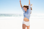 Happy mature woman in blue blouse and white shorts enjoying tropical beach vacation. Smiling young woman having fun on her vacation at sea. Joyful lady with red hair enjoying freedom with outstreched