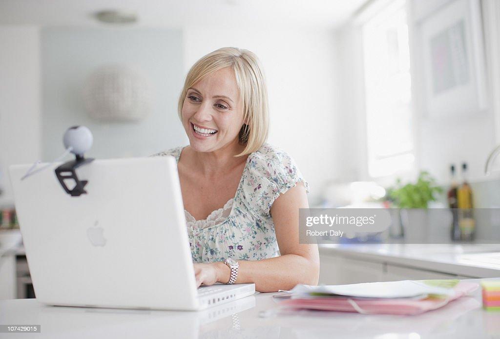 Smiling woman enjoying video chat on laptop