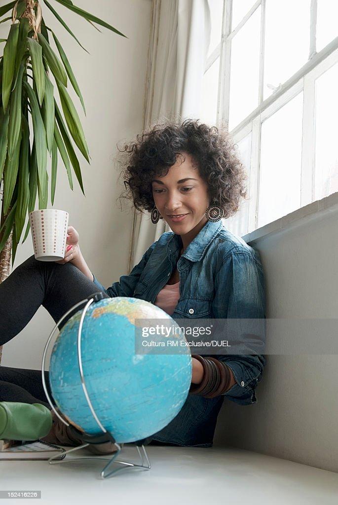 Smiling woman examining globe : Stock Photo