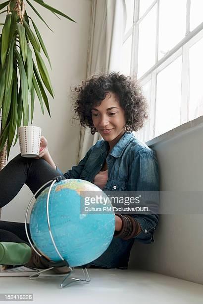 Smiling woman examining globe