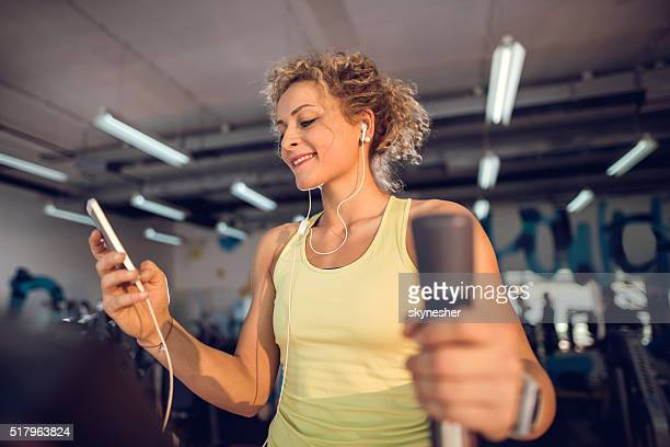 Smiling woman exercising in a gym and listening MP3 music.