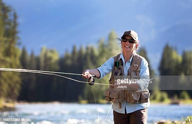 Frau Fliegenfischen von Regenbogenforelle auf einem British Columbia River.