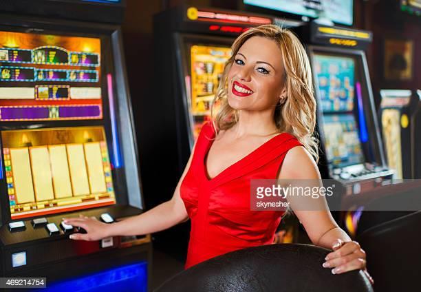 Donna sorridente gioco d'azzardo a slot machine del casinò.