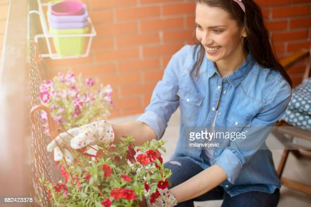 Smiling woman gardening on a balcony