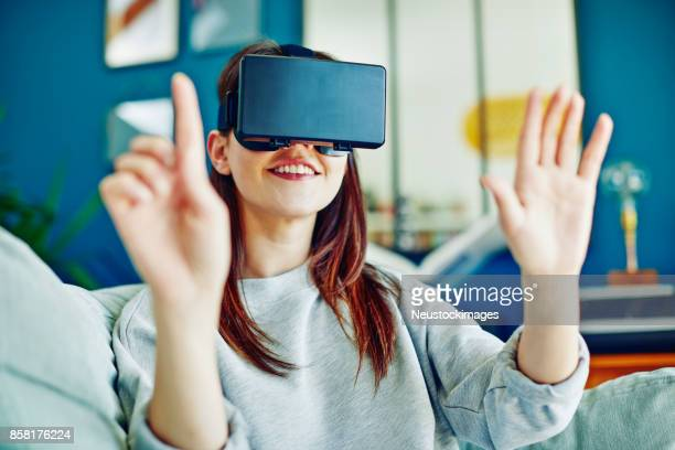 Smiling woman gesturing while using virtual reality headset at home
