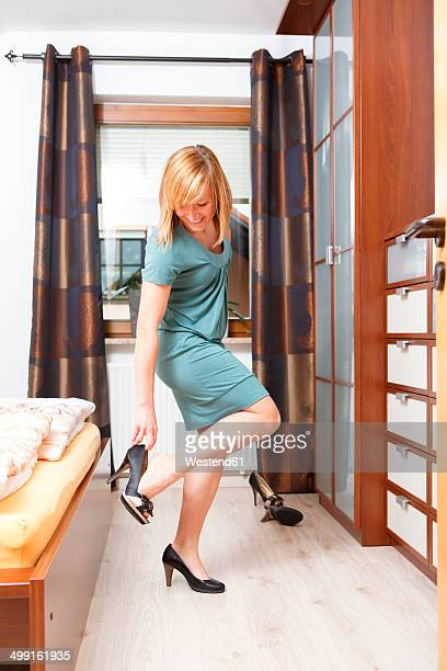 Smiling woman getting dressed with pumps in her bedroom
