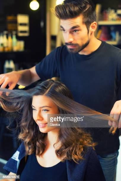 Smiling woman getting new hairstyle in hair salon