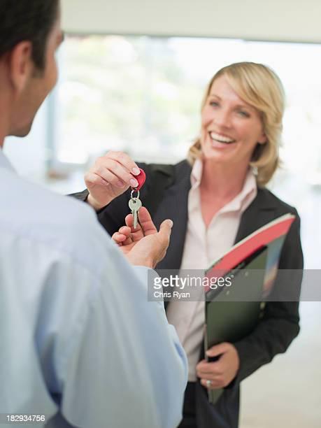 Smiling woman giving keys to man
