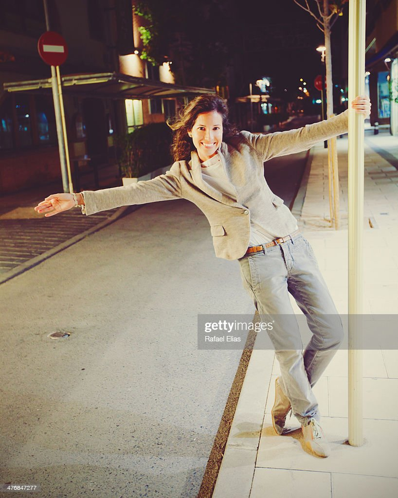 Smiling woman hanging from a pole