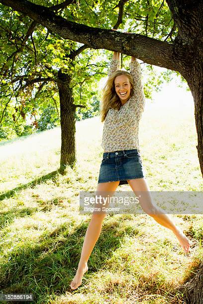Smiling woman hanging from tree