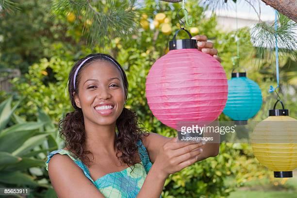 Smiling woman hanging paper lantern