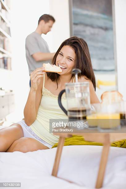 Smiling woman having breakfast in bed