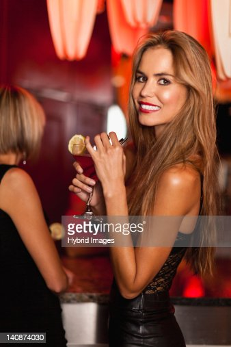 Smiling woman having cocktails in bar : Stock Photo