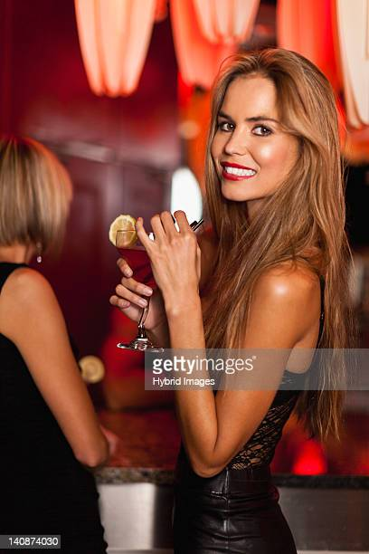 Smiling woman having cocktails in bar