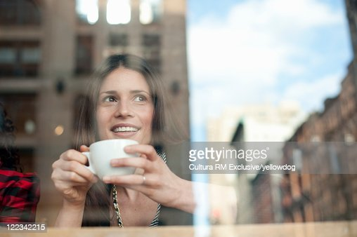 Smiling woman having coffee in cafe : Stock Photo