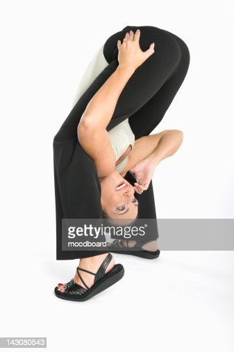 Smiling woman having conversation on cell phone while exercising : Stock Photo