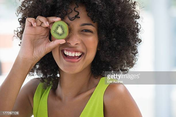 Smiling woman holding a kiwi fruit in front of her eye