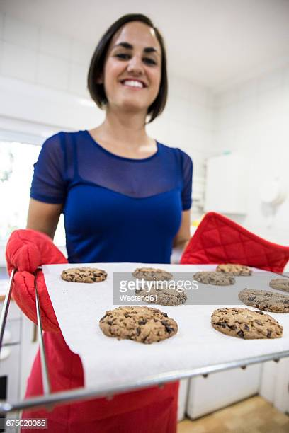 Smiling woman holding a tray of freshly baked cookies