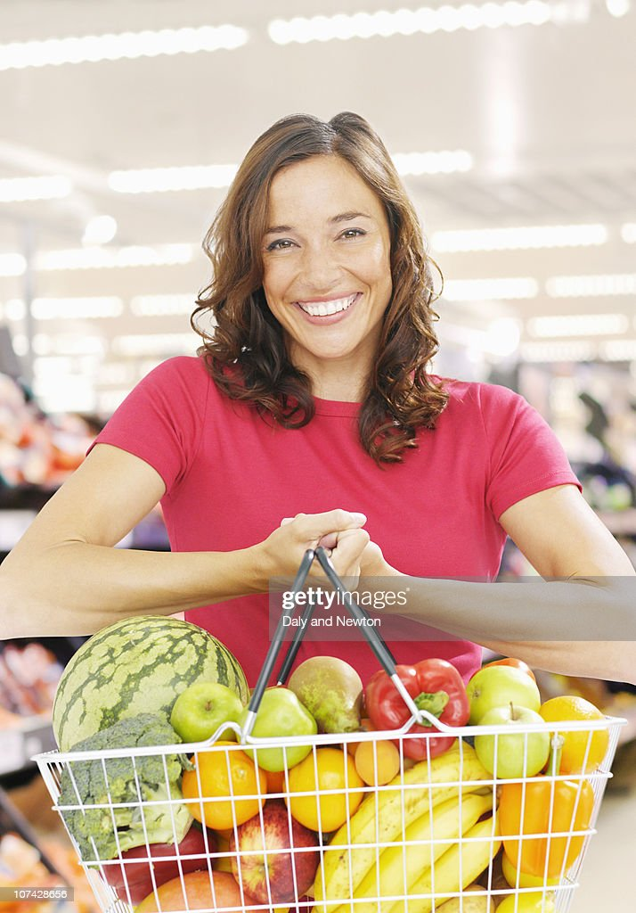Smiling woman holding basket full of fresh fruit and vegetables : Stock Photo