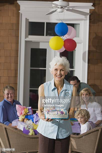 Smiling woman holding birthday cake