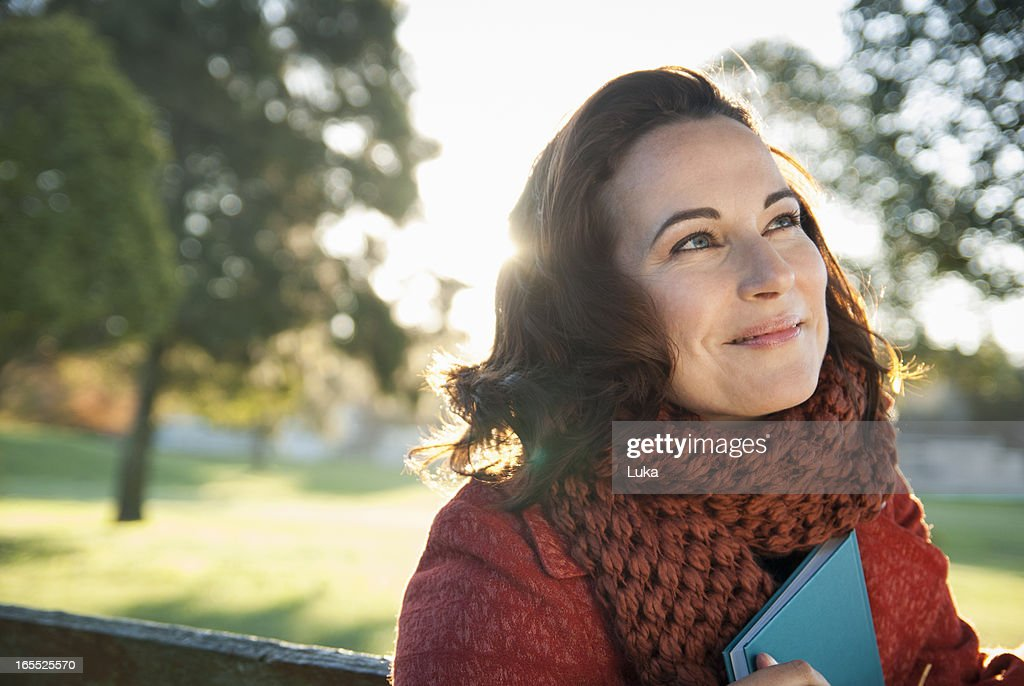 Smiling woman holding book outdoors