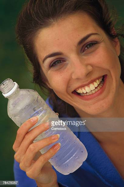 Smiling woman holding bottled water