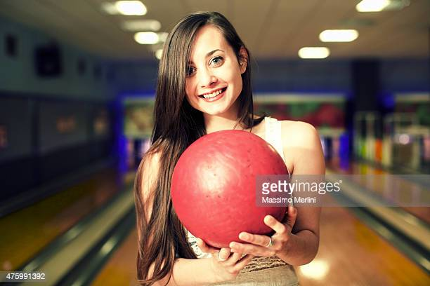 Smiling woman holding bowling ball at alley