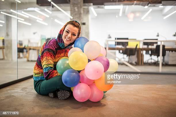 Sonriente mujer agarrando coloridos globos y mirando a la cámara.