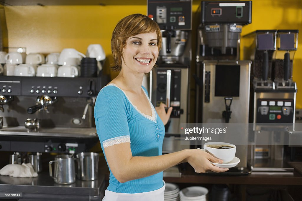 Smiling woman holding cup of coffee : Stock Photo