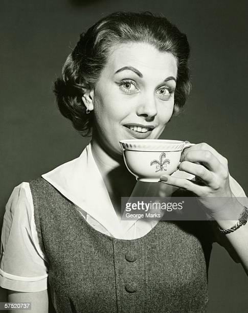 Donna sorridente con una tazza, in posa in studio (B & W), verticale