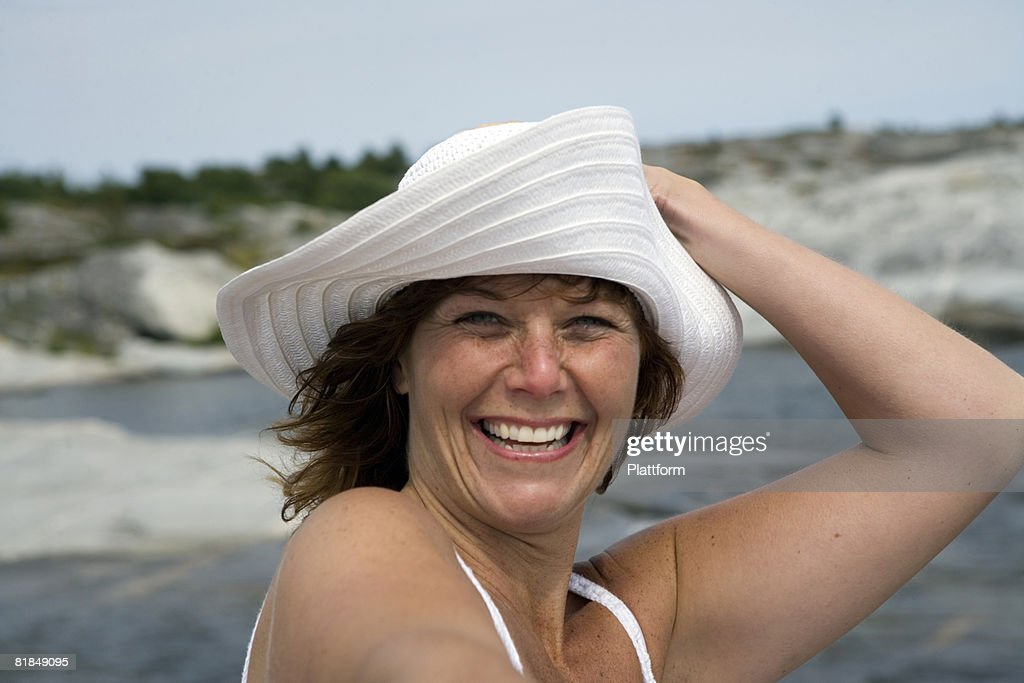 A smiling woman holding on to her hat Sweden. : Stock Photo