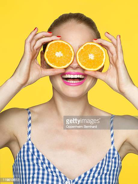 Smiling woman holding oranges over her eyes