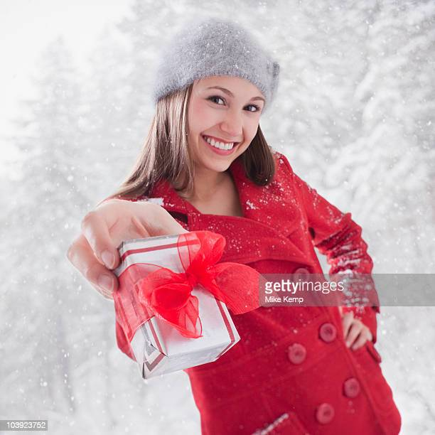 Smiling woman holding out a Christmas gift
