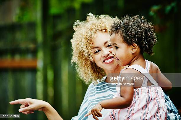 Smiling woman holding toddler niece during party