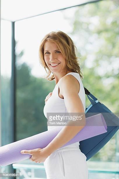 Smiling woman holding yoga mat