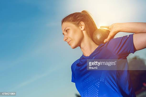 Smiling woman in a shot put against the sky.