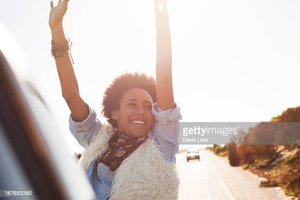 Smiling woman in back of truck with arms raised