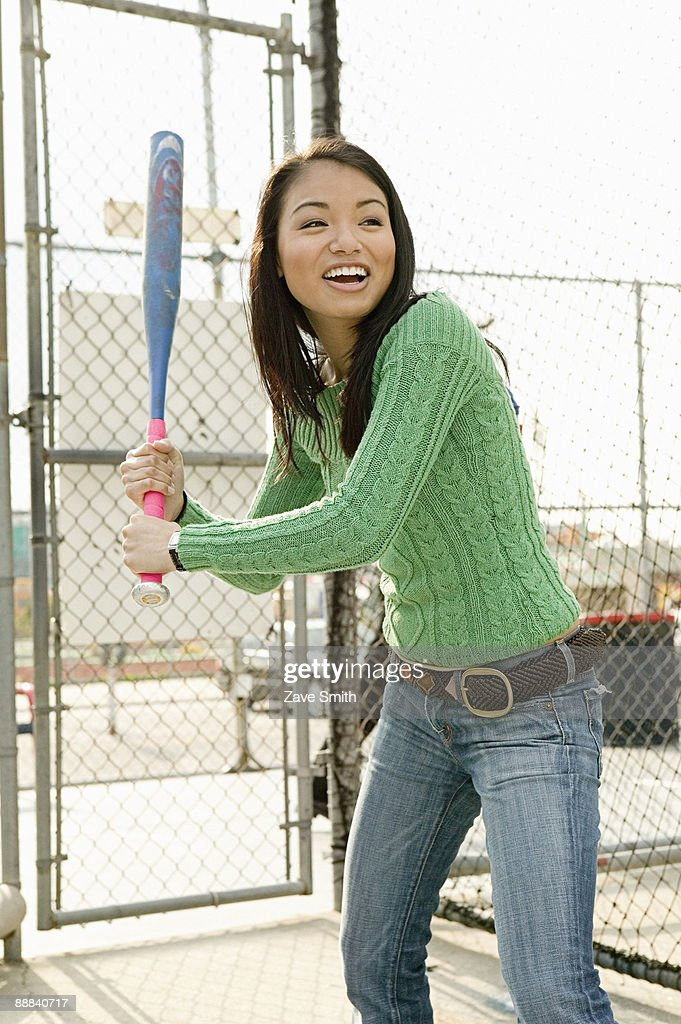Smiling woman in batting cage