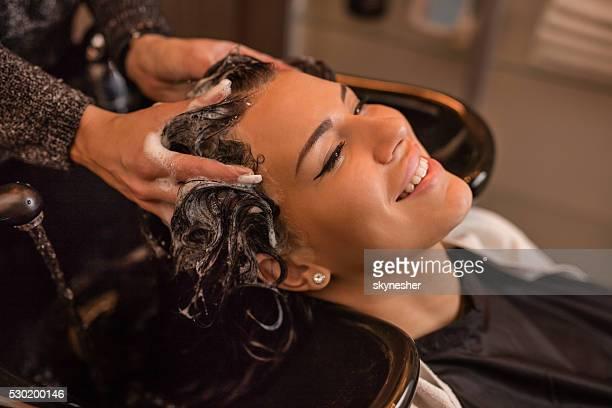 Smiling woman in hair salon washing hair.