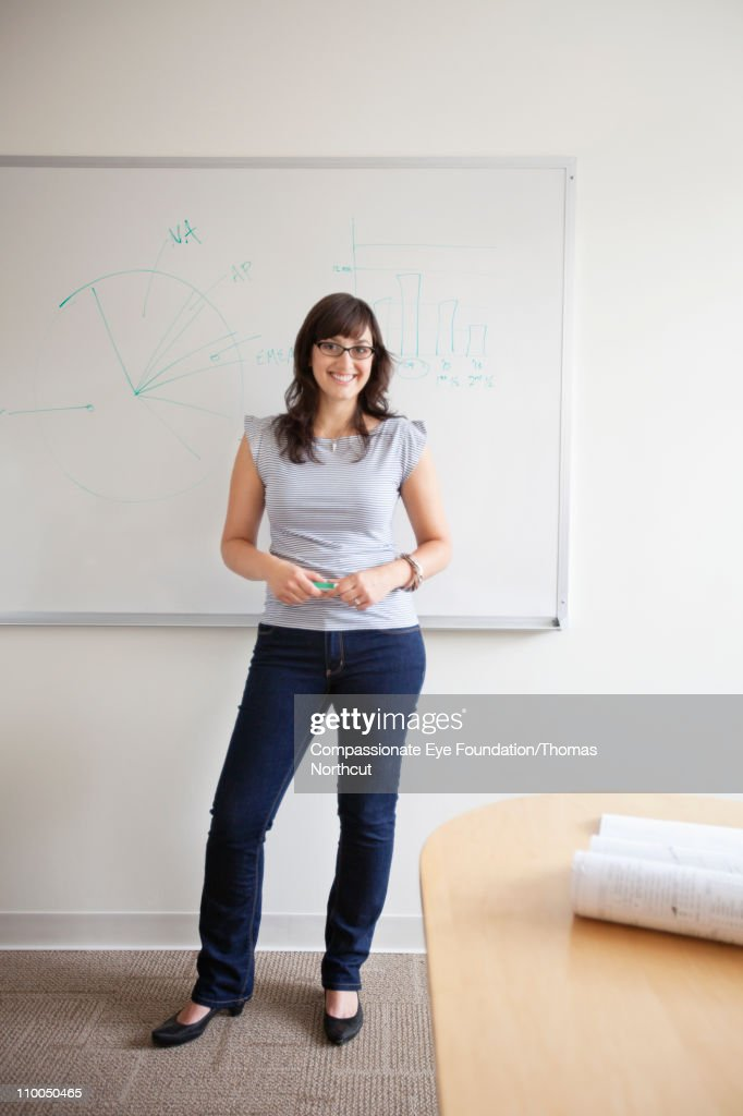 Smiling woman in jeans standing in an office : Stock Photo