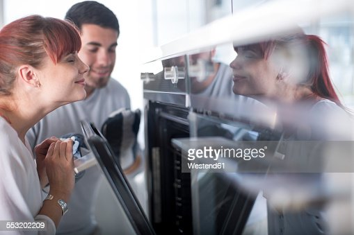 Smiling woman in kitchen at oven