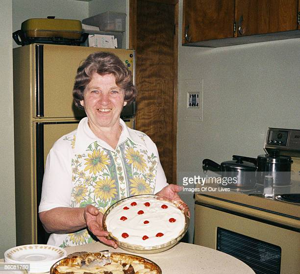 Smiling woman in kitchen holding pie