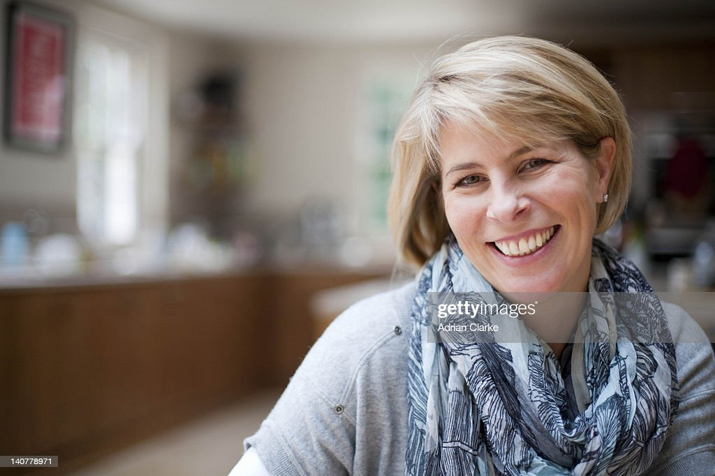 Smiling woman in kitchen : Stock Photo