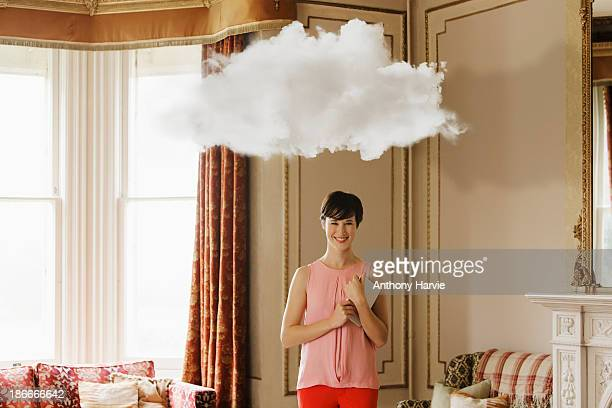 Smiling woman in living room with cloud above head