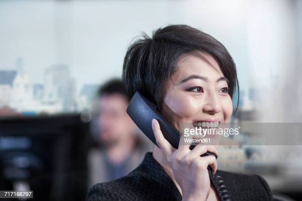 Smiling woman in office talking on phone