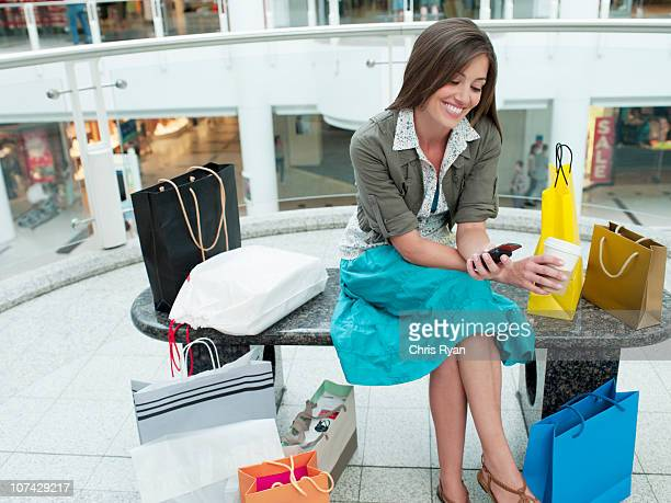 Smiling woman in shopping mall relaxing on bench