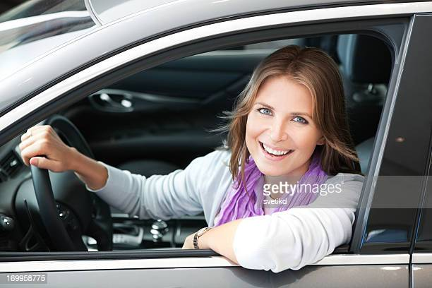 Smiling woman in stationary car