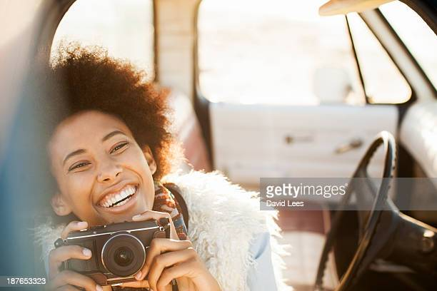 Smiling woman in truck taking photo